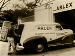 black and white picture of man opening the trunk of a arlex oil car