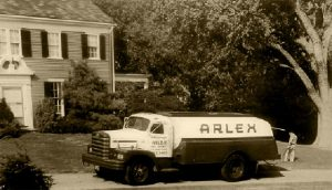 black and white picture of arlex oil truck parked in front of a house