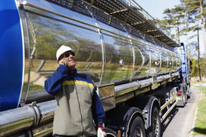 oil delivery truck with man on the phone in front of it
